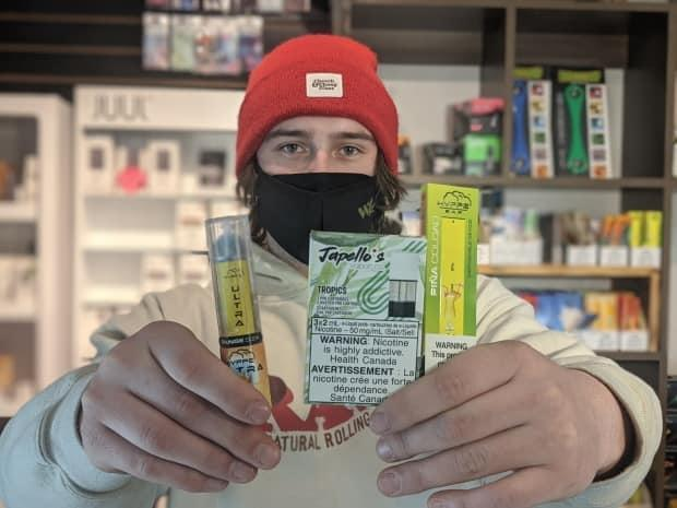 Manager J-K Thorne holds some of the flavoured products that will no longer be available at Wild Impulse.   (Shane Hennessey/CBC - image credit)