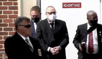 In this image from video, Gregory McMichael, second from right, is led by security officers from the Glynn County Courthouse in Brunswick, Ga., Wednesday, May 12, 2021. A Georgia judge will continue hearing legal motions Thursday in the murder case of three men facing a fall trial in the slaying of Ahmaud Arbery, a Black man who was chased and shot after being spotted running in the defendants' neighborhood. (AP Photo/Lewis M. Levine)