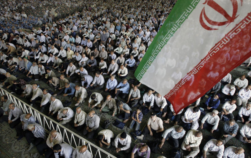 Iranian worshippers listen to a sermon during Friday prayers as an Iranian flag flutters at Tehran University in Tehran, Iran, Friday, July 6, 2012. Iranian Intelligence Minister Heidar Moslehi, unseen, delivered a speech during Friday prayers accusing French and German intelligence services of cooperating with the CIA to kill Iranian nuclear scientists. (AP Photo/Vahid Salemi)