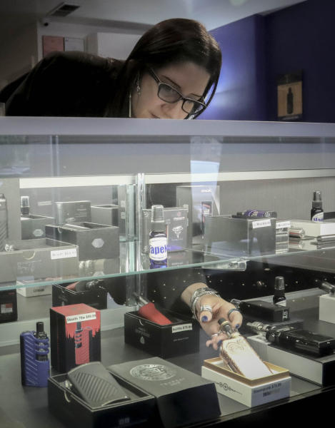 """In this Tuesday, Oct. 8, 2019, photo Spike Babaian, owner of several Vape New York stores, works in her East Harlem store in New York. Sales at small businesses that sell vaping products have plunged since August, when reports of vaping-related illnesses and deaths began. """"We can never undo the government going on the news and saying it's not safe to vape. The damage has been done,"""" says Babaian, who has been in business for eight years.  (AP Photo/Bebeto Matthews)"""