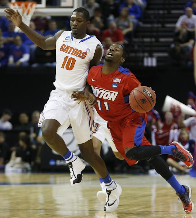 Dayton guard Scoochie Smith (11) moves the ball against Florida forward Dorian Finney-Smith (10) during the first half in a regional final game at the NCAA college basketball tournament, Saturday, March 29, 2014, in Memphis, Tenn. (AP Photo/John Bazemore)
