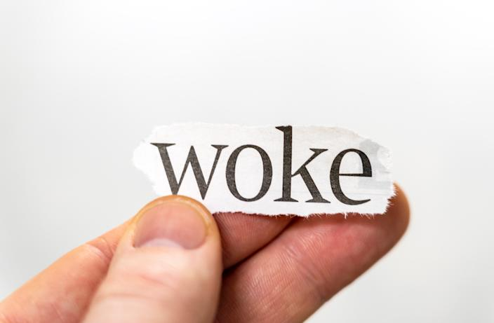Macro image of a person holding up the word 'woke'.