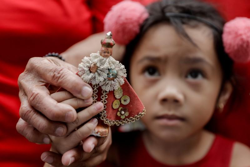 A girl holds a small replica of Baby Jesus during Catholic mass to celebrate its feast day in an evacuation center