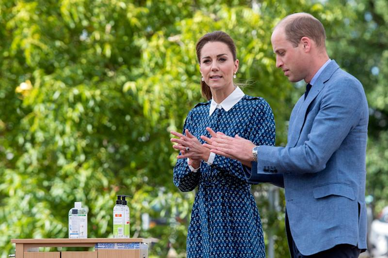 Prince William and Kate, Duchess of Cambridge apply hand sanitizer during a visit to Queen Elizabeth Hospital as part of the NHS birthday celebrations Sunday.