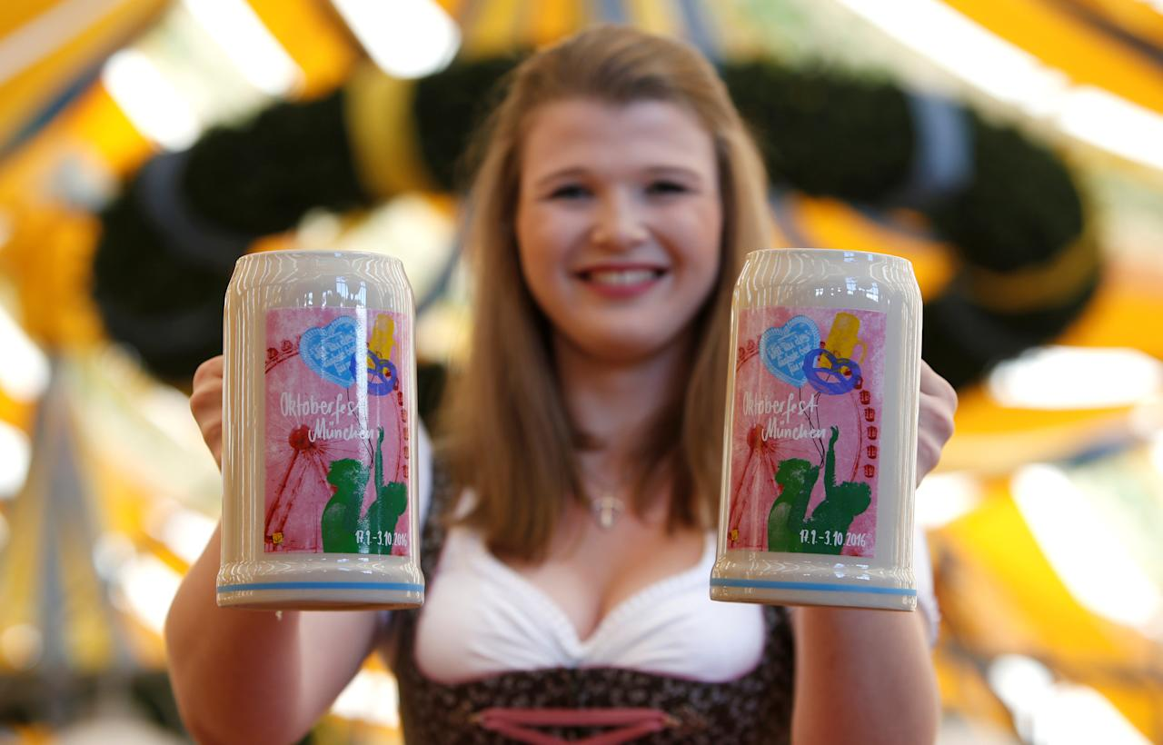 Model Sarah wears traditional Bavarian costume as she holds the official Oktoberfest beer mugs during a presentation in Munich, Germany August 23, 2016. REUTERS/Michaela Rehle