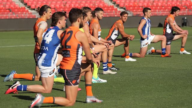 Players, coaches and umpires take a knee before Greater Western Sydney's clash with North Melbourne. (Photo by Matt King/AFL Photos/Getty Images)