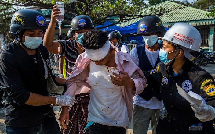An injured protester receives medical attention after police and military forces cracked down on a protest - THE NEW YORK TIMES