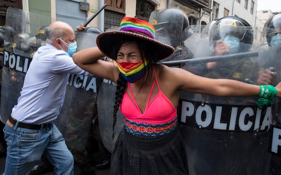 Supporters of Peru's former President Martin Vizcarra are stopped by police from marching to Congress where lawmakers voted the previous night to remove Vizcarra from office - Rodrigo Abd/AP