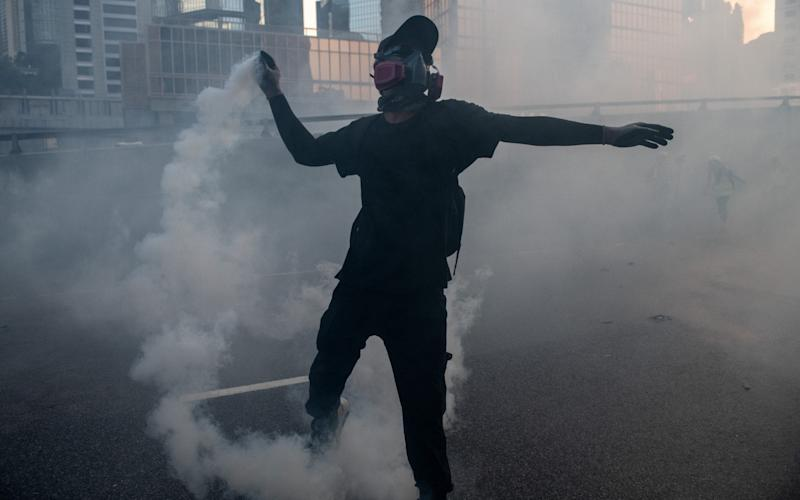 A pro-democracy protester throws a police teargas cartridge back at officers on September 15 - Getty Images AsiaPac