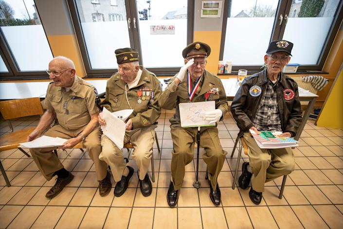John Pildner Sr. salutes the schoolchildren of the Noville, Belgium, public school during a visit Dec. 13, 2019, as part of the 75th Anniversary of the Battle of the Bulge. From left to right are, Frank Riesinger, George Merz, Pidner and Robert Izumi, a Vietnam veteran.