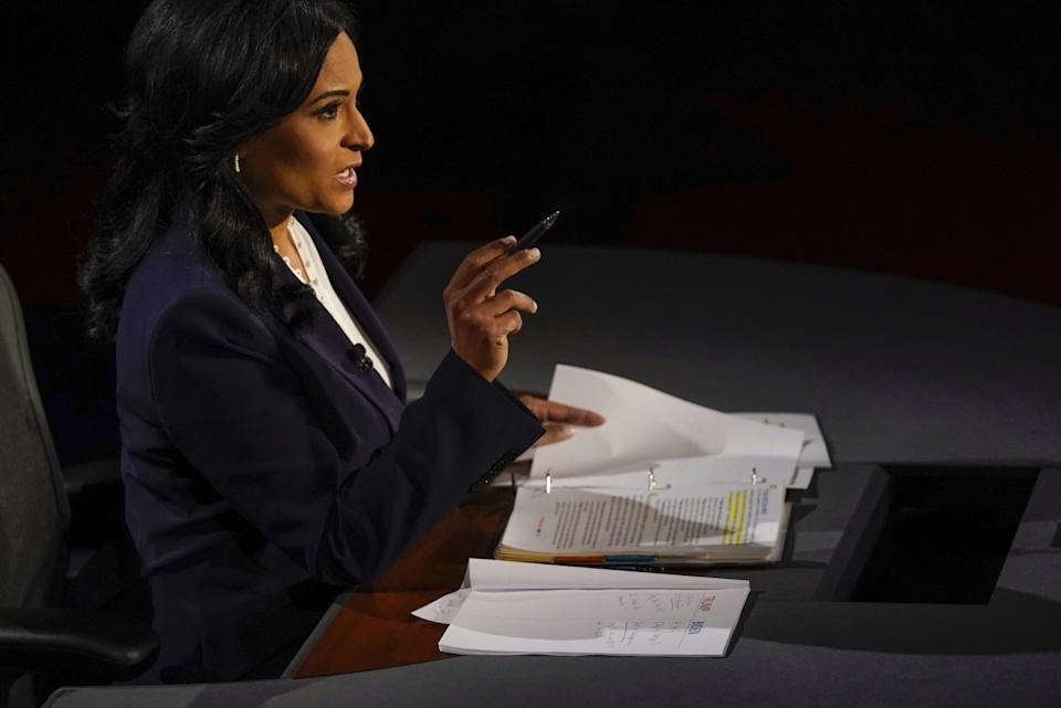 Moderator Kristen Welker gestures with a pen in her hand sitting in front of notes on her desk