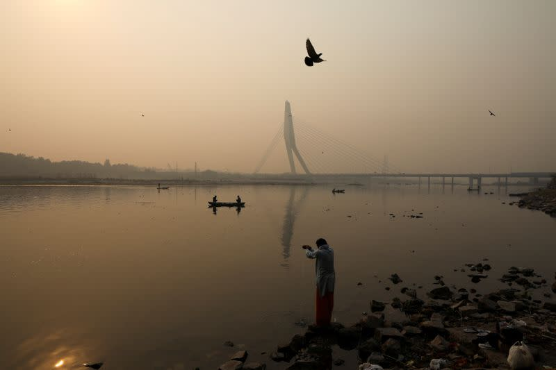 A man prays on the banks of Yamuna river, on a smoggy morning in New Delhi