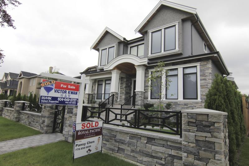 Realtors' signs are hung outside a newly sold property in a Vancouver neighborhood
