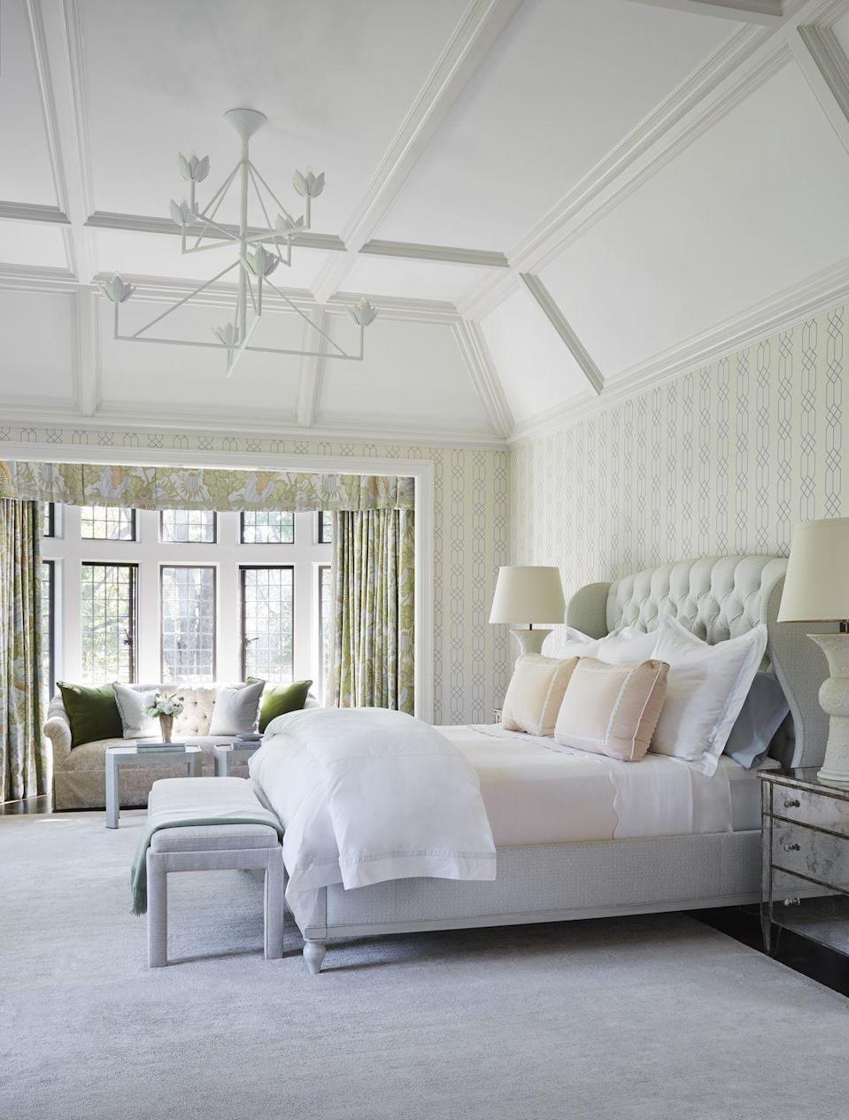 "<p>This inviting bedroom suite in a <a href=""https://www.veranda.com/decorating-ideas/a35369881/carrier-and-company-bronxville-house-tour/"" rel=""nofollow noopener"" target=""_blank"" data-ylk=""slk:Bronxville, New York home"" class=""link rapid-noclick-resp"">Bronxville, New York home</a> designed by <a href=""https://www.veranda.com/decorating-ideas/a35369881/carrier-and-company-bronxville-house-tour/"" rel=""nofollow noopener"" target=""_blank"" data-ylk=""slk:Carrier & Company"" class=""link rapid-noclick-resp"">Carrier & Company</a> is a perfect example of the house's balance of Old-World sophistication and a youthful spirit. A white, sculptural chandelier and two overside lamps residing on metallic bedside tables creates a variety of lighting options at night while Tudor-style iron windows let in just the right amount of light to keep this room feeling vibrant and welcoming. </p>"