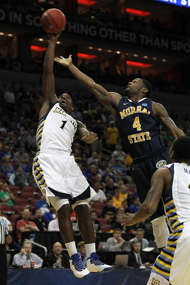 LOUISVILLE, KY - MARCH 17: Darius Johnson-Odom #1 of the Marquette Golden Eagles goes up for a rebound over Latreze Mushatt #4 of the Murray State Racers in the first half during the third round of the 2012 NCAA Men's Basketball Tournament at KFC YUM! Center on March 15, 2012 in Louisville, Kentucky. (Photo by Jonathan Daniel/Getty Images)