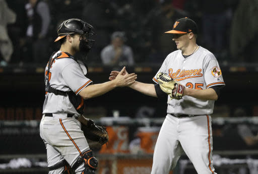 Baltimore Orioles catcher Andrew Susac, left, and relief pitcher Brad Brach celebrate the team's 3-2 win over the Chicago White Sox after a baseball game Monday, May 21, 2018, in Chicago. (AP Photo/Charles Rex Arbogast)