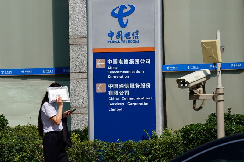 FILE PHOTO: Woman shields herself from the sun as she walks past an office building of China Telecom, in Beijing