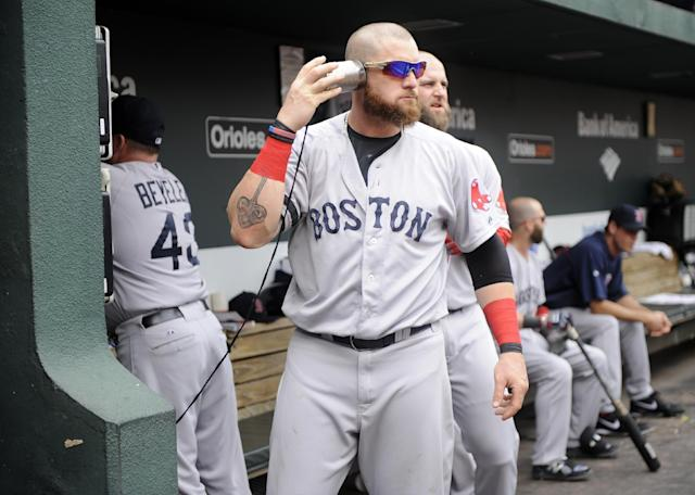 Boston Red Sox's Jonny Gomes plays with a can attached to a string leading to the dugout phone before a baseball game against the Baltimore Orioles, Sunday, July 28, 2013, in Baltimore. (AP Photo/Nick Wass)