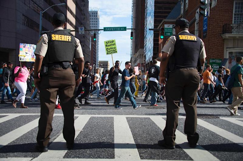 Police stand watch as protesters march through the streets in Baltimore on May 2, 2015, a day after six police officers were charged over the death of Freddie Gray (AFP Photo/Jim Watson)