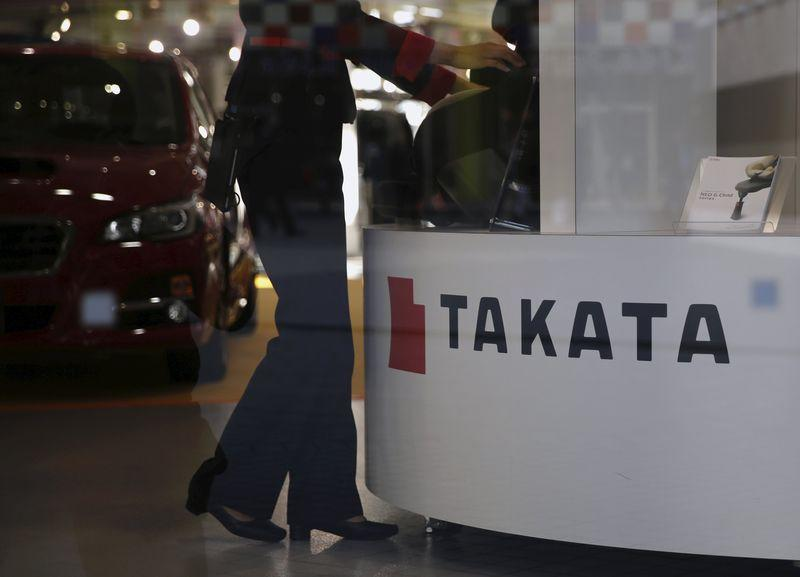 A woman stands next to a logo of Takata Corp at a showroom for vehicles in Tokyo