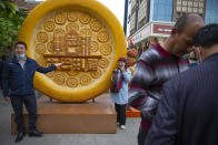 Visitors pose for photos with a giant plastic sculpture of a piece of Uyghur's naan bread at the International Grand Bazaar in Urumqi in northwestern China's Xinjiang Uyghur Autonomous Region, during a government organized visit, on April 22, 2021. Four years after Beijing's brutal crackdown on largely Muslim minorities native to Xinjiang, Chinese authorities are dialing back the region's high-tech police state and stepping up tourism. But even as a sense of normality returns, fear remains, hidden but pervasive. (AP Photo/Mark Schiefelbein)