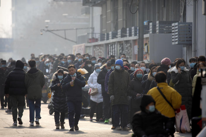 People wearing face masks to protect against the spread of the coronavirus line up for mass COVID-19 testing in a central district of Beijing, Friday, Jan. 22, 2021. Beijing has ordered fresh rounds of coronavirus testing for about 2 million people in the downtown area following new cases in the Chinese capital. (AP Photo/Mark Schiefelbein)