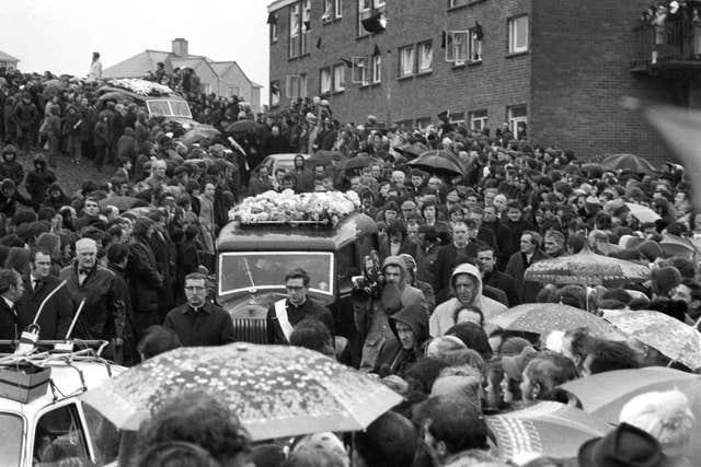 A silent crowd form a cordon 10 or more deep, lining both sides of the 250 yards of road leading from St Mary's Church, Creggan Hill to the cemetery, to watch the funeral procession of the 13 who died on Bloody Sunday (Archive/PA)