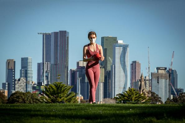 A woman plays football in the afternoon sun at Princes Park in Carlton.