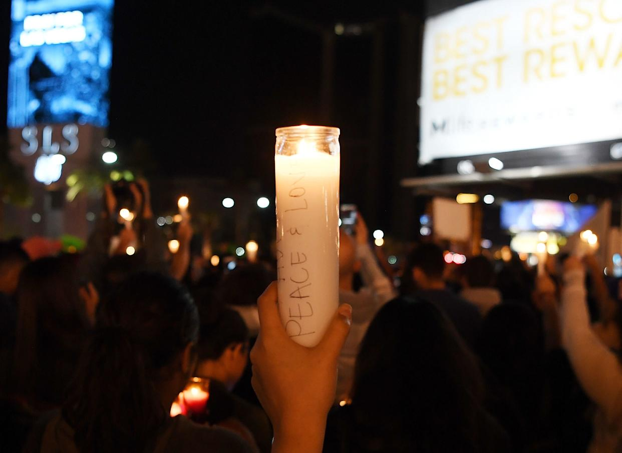 People hold up candles during a vigil on the Las Vegas strip.