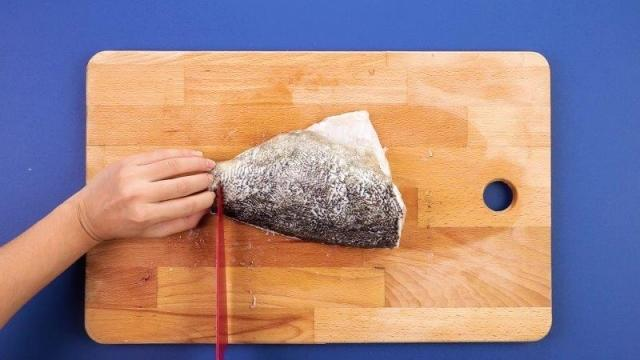 Slicing fish on a wooden chopping board with red knife