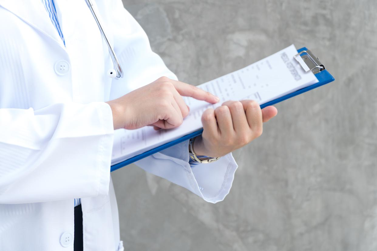 Close-up view of hand woman doctor holding blue clipboard and reading something. Healthcare and medical concept