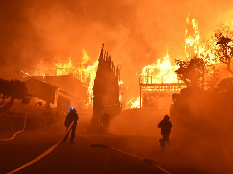 Firefighters work to put out a blaze burning homes in Ventura, California: Ryan Cullom/Ventura County Fire Department via AP