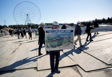 A man holds a conceptional drawing at the construction site of the Kasai Canoe Slalom Centre for Tokyo 2020 Olympic games in Tokyo, Japan February 12, 2019. REUTERS/Issei Kato