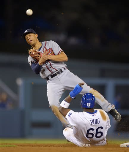 Los Angeles Dodgers' Yasiel Puig, below, is forced out at second as Atlanta Braves shortstop Andrelton Simmons attempts to throw out Nick Punto at first during the eighth inning of their baseball game, Saturday, June 8, 2013, in Los Angeles. The ball was overthrown and Punto advanced to second on the play. (AP Photo/Mark J. Terrill)