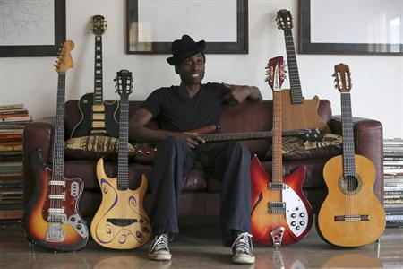 Nigerian musician Keziah Jones sits on a sofa between guitars during an interview with Reuters at his home in Lagos