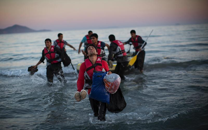 Migrants come ashore after crossing by dinghy from the Turkish coast to the Greek island of Kos. The photograph was taken in August 2015. - 2015 Getty Images
