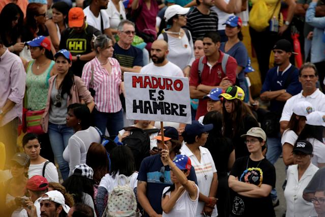 """<p>Opposition supporters block an avenue while rallying against President Nicolas Maduro carrying a sign that reads """"Maduro is hunger"""" in Caracas, Venezuela, May 15, 2017. (REUTERS/Marco Bello/Reuters) </p>"""