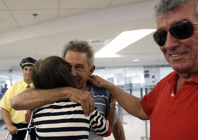 In this Sept. 11, 2013, photo, Benito Perez, center, is greeted by his friends Rogelia Ventura and Luis Ventura, right, at his arrival at Miami International Airport, in Miami. Perez, who had never been on a plane, is one of thousands of Cubans traveling under new laws making travel slightly easier. (AP Photo/Alan Diaz)