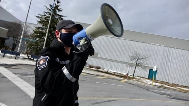 A City of Ottawa bylaw officer uses a megaphone to instruct people at the Nepean Sportsplex vaccination clinic on March 12, 2021. The city says people should wait until the province's website launches Monday to book an appointment as all the weekend appointment spots there have been snatched up. (Jonathan Dupaul/CBC - image credit)