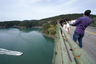 A family walks along the narrow sidewalk of the Deception Pass Bridge, a 976-foot span about 180-feet above the waters below, where work to replace corroded steel and paint the structure continues Thursday, April 29, 2021, in Deception Pass, Wash. Raising state taxes to improve roads and bridges is one of the few things many Republican and Democratic lawmakers have agreed on in recent years. Those efforts have slowed to a crawl this year, even as lawmakers acknowledge a widening gap between needed work and the money to pay for it. (AP Photo/Elaine Thompson)