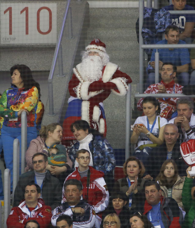 A hockey fan dressed as Grandfather Frost watches play between Russia and Slovenia in the first period of a men's ice hockey game at the 2014 Winter Olympics, Thursday, Feb. 13, 2014, in Sochi, Russia. (AP Photo/Julio Cortez)