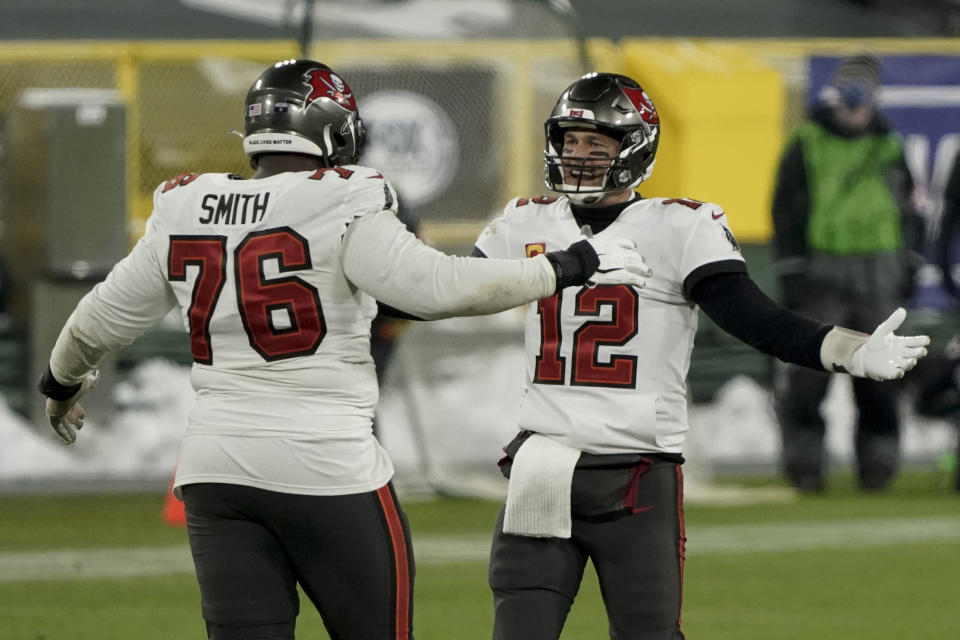 Tampa Bay Buccaneers quarterback Tom Brady celebrates with Donovan Smith after winning the NFC championship NFL football game in Green Bay, Wis., Sunday, Jan. 24, 2021. The Buccaneers defeated the Packers 31-26 to advance to the Super Bowl. (AP Photo/Morry Gash)