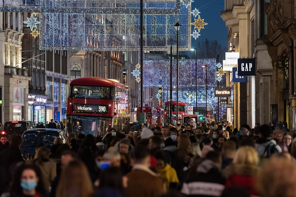 Crowds of shoppers and commuters walk along Oxford Street decorated with festive illuminations ahead of introduction of tougher coronavirus restrictions in the run up to Christmas, on 15 December, 2020 in London, England. From tomorrow, Greater London, as well as parts of Essex and Hertfordshire, will move into Tier 3 coronavirus restrictions resulting in closing of pubs, bars, restaurants, hotels and indoor entertainment venues such as theatres and cinemas, as the infection rates are well above the national average and continue to rise. (Photo by WIktor Szymanowicz/NurPhoto via Getty Images)