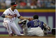 Colorado Rockies' Dexter Fowler (24) is tagged out by Atlanta Braves shortstop Andrelton Simmons, left, while trying to steal second base in the first inning of a baseball game in Atlanta, Wednesday, July 31, 2013. (AP Photo/John Bazemore)