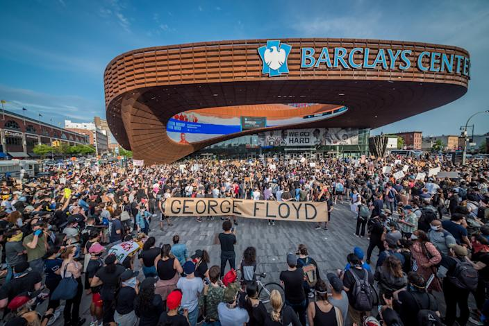 Protesters holding a giant banner reading GEORGE FLOYD outside the Barclays Center. Hundreds of protesters made their way toward Barclays Center in Brooklyn to demonstrate against police brutality in the wake of George Floyd's death while in police custody in Minneapolis. (Erik McGregor/LightRocket via Getty Images)
