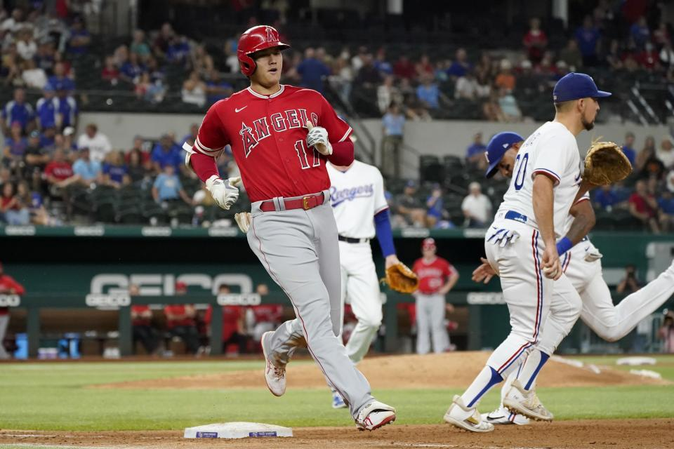 Los Angeles Angels' Shohei Ohtani (17) runs out a ground out to second as Texas Rangers first baseman Nathaniel Lowe, right, stands by the bag in the seventh inning of a baseball game in Arlington, Texas, Wednesday, Sept. 29, 2021. (AP Photo/Tony Gutierrez)