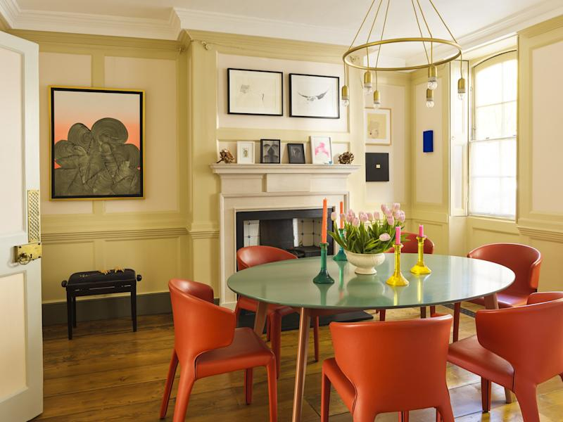 """The Hampstead, London, dining room in a 1735 home owned by architect and designer Bruce Irwin and his husband, Pedro Font-Alba, is the first space that visitors encounter, and it sets a playful tone for the house. Hot orange and """"insanely comfortable"""" Cassina Hola chairs, from Aram, cluster around a Pinch Design table under a light by Adolf Loos for Woka Lamps. The large work in acrylic to the left of the fireplace is by Spanish artist Alan Sastre."""
