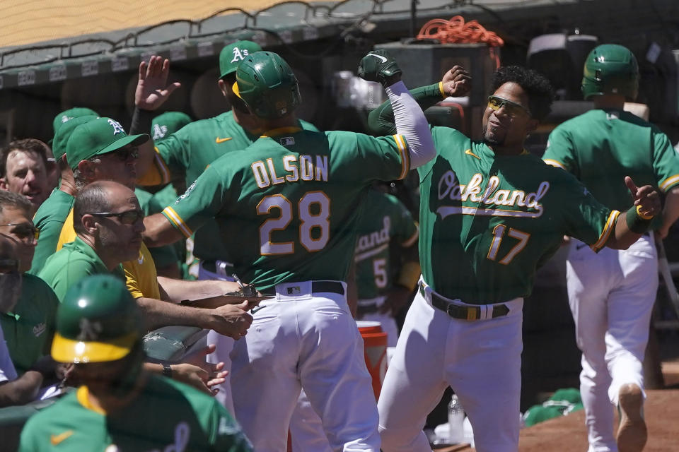 Oakland Athletics' Matt Olson (28) is congratulated by Elvis Andrus (17) after hitting a home run against the Kansas City Royals during the fifth inning of a baseball game in Oakland, Calif., Sunday, June 13, 2021. (AP Photo/Jeff Chiu)