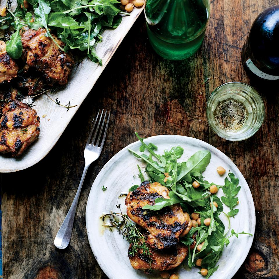 """Chicken thighs are appealingly fatty, but this can sometimes cause flareups when grilling. Bank the coals before igniting so that you have a cooler side, and move the chicken there if needed. <a href=""""https://www.epicurious.com/recipes/food/views/grilled-chicken-with-arugula-and-warm-chickpeas-51234650?mbid=synd_yahoo_rss"""">See recipe.</a>"""