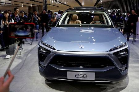 FILE PHOTO: Visitors check NIO ES8 displayed during a media preview of the Auto China 2018 motor show in Beijing, China April 25, 2018. REUTERS/Damir Sagolj/File Photo